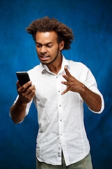 Verärgerter hübscher afrikanischer mann, der telefon über blaue wand betrachtet.