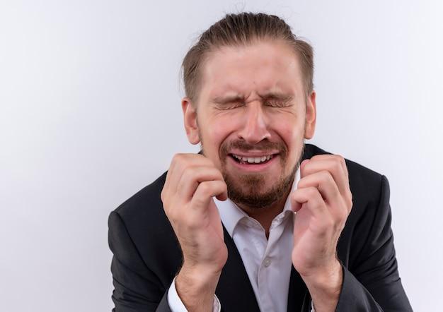 Verärgerter hübscher geschäftsmann, der anzug mit geschlossenen augen trägt, die über weißem hintergrund stehen weinen