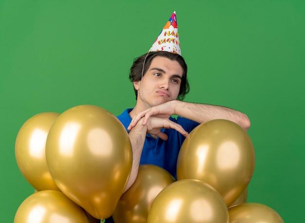 Verärgerter hübscher kaukasischer mann mit geburtstagsmütze steht mit heliumballons