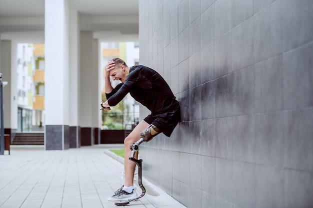 Verärgerter hübscher kaukasischer sportler mit künstlichem bein, das sich an die wand lehnt, kopf hält und armbanduhr betrachtet.