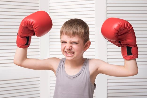 Verärgerter junge in den roten boxhandschuhen.