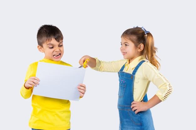 Verärgerter junge mit weißem papier für ihre werbung. mädchen mit der schere auf einem weißen hintergrund.