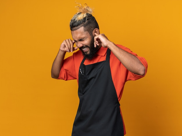 Verärgerter junger afroamerikanischer männlicher barbier in uniform, der finger in die ohren steckt, mit geschlossenen augen isoliert auf orangefarbener wand mit kopierraum