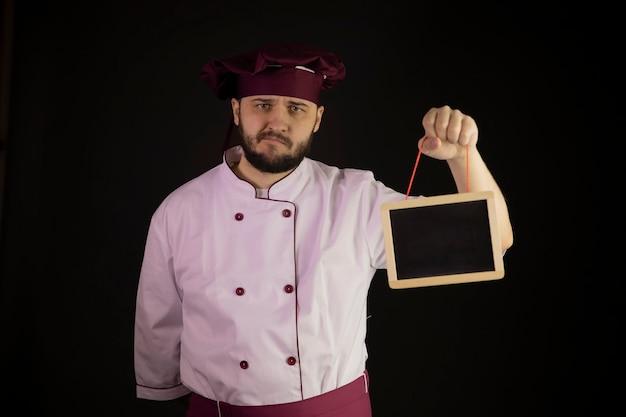 Verärgerter junger bärtiger männlicher koch in uniform zeigt leere tafel