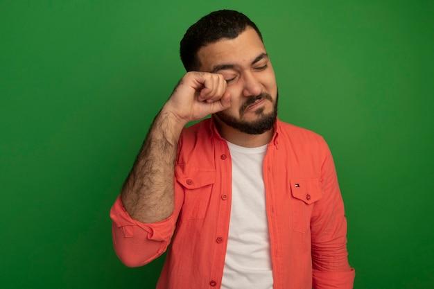 Verärgerter junger bärtiger mann im orangefarbenen hemd, das weint und seine augen reibt, die über grüner wand stehen