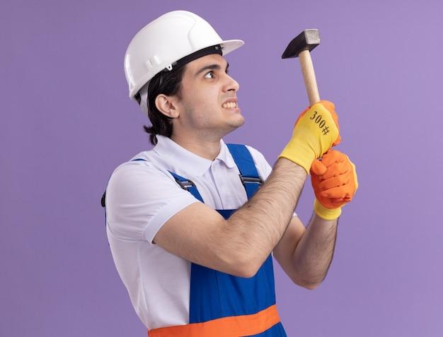 Verärgerter junger baumeistermann in der bauuniform und im schutzhelm in den gummihandschuhen, die hammer halten, der sie mit genervtem ausdruck betrachtet, der über lila wand steht