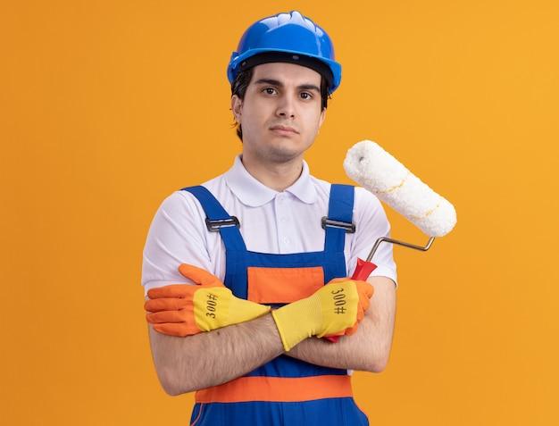 Verärgerter junger baumeistermann in der bauuniform und im sicherheitshelm, die gummihandschuhe halten, die farbroller halten, der vorne mit ernstem sicherem ausdruck steht, der über orange wand steht
