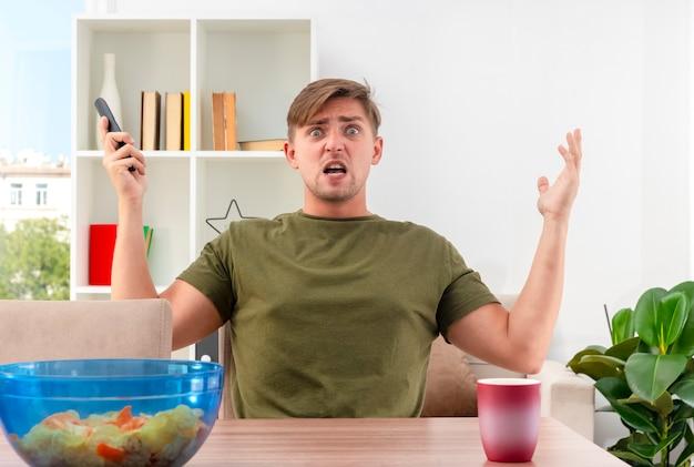 Verärgerter junger blonder gutaussehender mann sitzt am tisch mit schüssel schüssel chips und tasse hebt die hände hoch und hält tv-fernbedienung im wohnzimmer