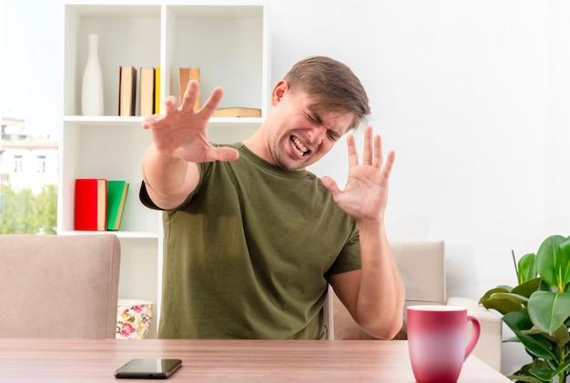 Verärgerter junger blonder gutaussehender mann sitzt am tisch mit tasse und telefon, die hände innerhalb des wohnzimmers heben
