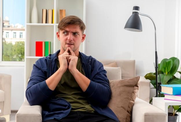 Verärgerter junger blonder gutaussehender mann sitzt auf sessel, der hände zusammenhält und seite im wohnzimmer betrachtet
