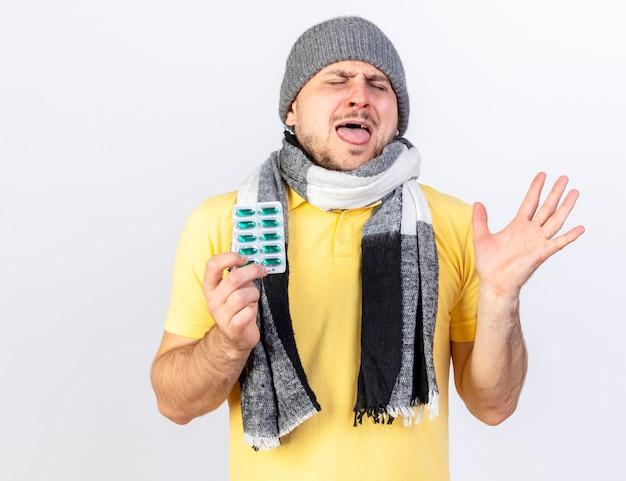 Verärgerter junger blonder kranker mann, der wintermütze und schal trägt, steht mit erhabener hand, die packung der medizinischen pillen hält, die auf weißer wand isoliert werden