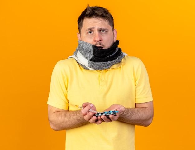 Verärgerter junger blonder kranker slawischer mann, der mund mit schal bedeckt