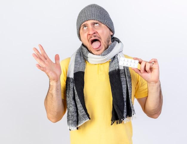 Verärgerter junger blonder kranker slawischer mann, der wintermütze und schal trägt, steht mit erhabener hand und hält packung der medizinischen pillen, die lokal auf weißer wand mit kopienraum suchen