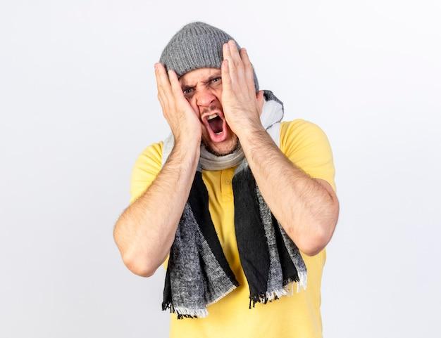Verärgerter junger blonder kranker slawischer mann, der wintermütze und schal trägt