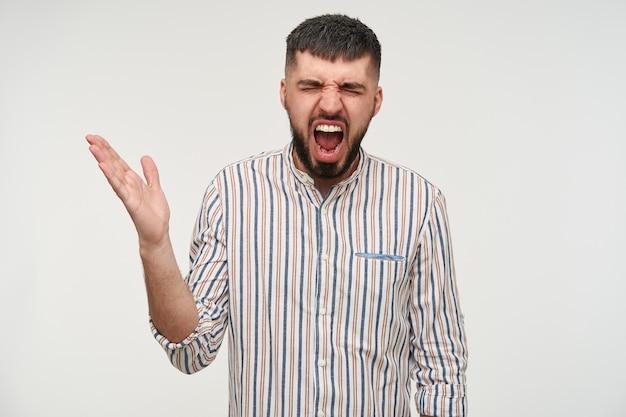 Verärgerter junger dunkelhaariger hübscher mann mit kurzem haarschnitt, der die augen geschlossen hält, während er schreit und affektiv seine hand hebt, isoliert über der weißen wand