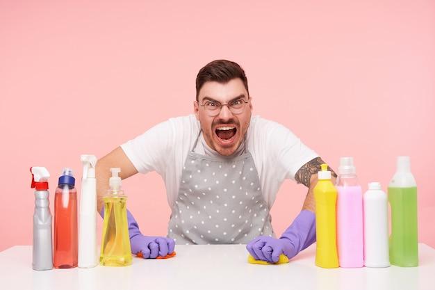 Verärgerter junger dunkelhaariger unrasierter mann in gläsern, der müde ist, nachdem er das haus geputzt hat und wütend beim waschen des tisches schreit, isoliert auf rosa