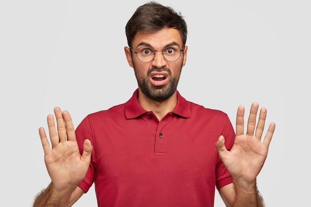 Verärgerter junger emotionaler mann, der gegen die weiße wand aufwirft