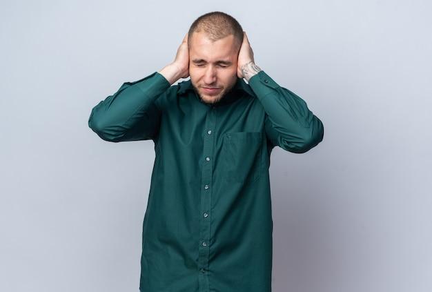 Verärgerter junger gutaussehender kerl, der grünes hemd trägt, bedeckte ohren mit händen
