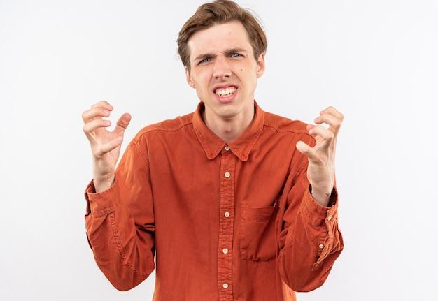 Verärgerter junger gutaussehender kerl mit rotem hemd, das hände um das gesicht hält, isoliert auf weißer wand?