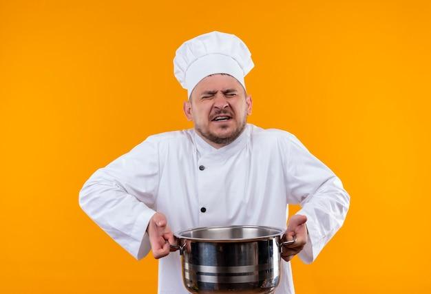 Verärgerter junger gutaussehender koch in kochuniform, der kessel mit geschlossenen augen an isolierter orangefarbener wand hält