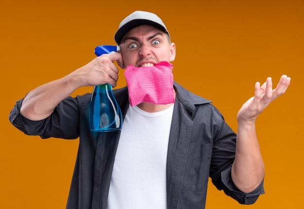 Verärgerter junger gutaussehender putzmann, der t-shirt und kappe hält lappen im mund hält sprühflasche auf schläfe isoliert auf orange wand