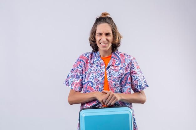Verärgerter junger gutaussehender reisender, der den koffer unglücklich und frustriert mit etwas hält, das die augen geschlossen hält