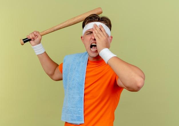 Verärgerter junger gutaussehender sportlicher mann, der stirnband und armbänder mit handtuch auf schulter trägt, das baseballschläger anhebt, der bereit ist, jemanden zu schlagen, der hand auf auge lokalisiert auf olivgrün setzt