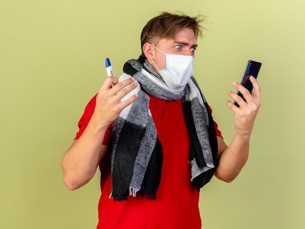Verärgerter junger hübscher blonder kranker mann, der maske und schal hält, die thermometer und handy halten, das telefon lokalisiert auf olivgrüner wand betrachtet