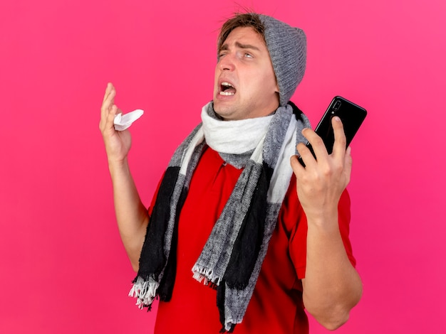 Verärgerter junger hübscher blonder kranker mann, der wintermütze und schal hält, die handy und serviette halten, die oben auf rosa wand suchen