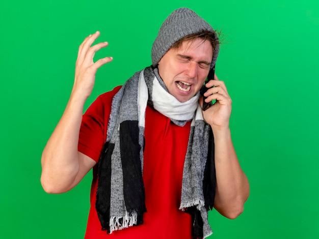Verärgerter junger hübscher blonder kranker mann, der wintermütze und schal trägt, die am telefon sprechen, das hand in luft mit geschlossenen augen hält, die auf grüner wand mit kopienraum lokalisiert werden