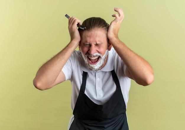 Verärgerter junger hübscher friseur, der uniform trägt, die seinen kopf mit geschlossenen augen und mit dem rasiermesser in der hand lokalisiert auf olivgrün hält