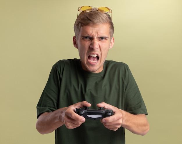 Verärgerter junger hübscher kerl, der grünes hemd mit brille auf kopf spielt, der auf gamecontroller-joystick spielt, der auf olivgrüner wand lokalisiert wird