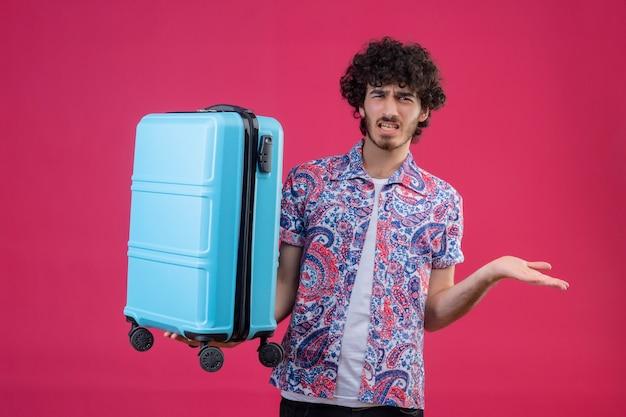 Verärgerter junger hübscher lockiger reisender mann, der koffer hält und leere hand auf lokalisiertem rosa raum zeigt