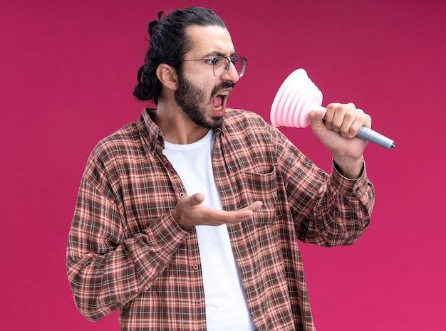 Verärgerter junger hübscher putzmann, der t-shirt hält und kolben lokalisiert auf rosa wand hält