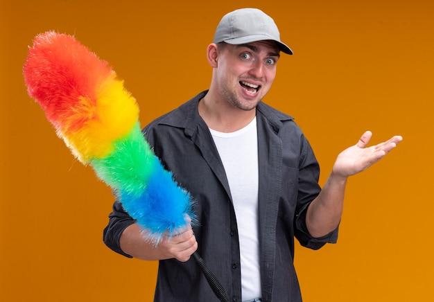 Verärgerter junger hübscher putzmann, der t-shirt und kappe hält, die staubwedel-ausbreitungshand lokalisiert auf orange wand hält