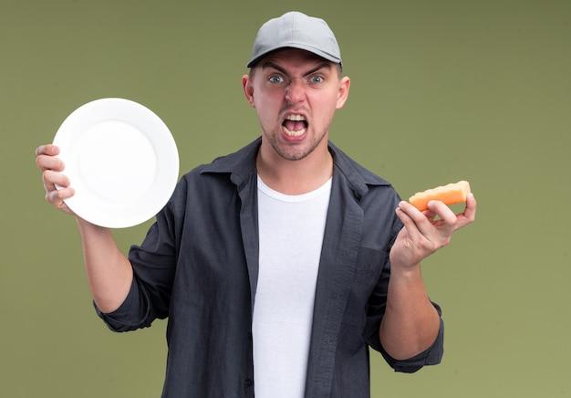 Verärgerter junger hübscher reinigungsmann, der t-shirt und kappenhalteplatte mit schwamm trägt, der auf olivgrüner wand lokalisiert wird