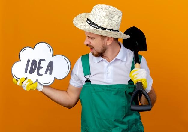 Verärgerter junger hübscher slawischer gärtner in der uniform, die hut und gartenhandschuhe trägt, die spaten und ideenblase halten, die ideenblase lokalisiert auf orange wand betrachten