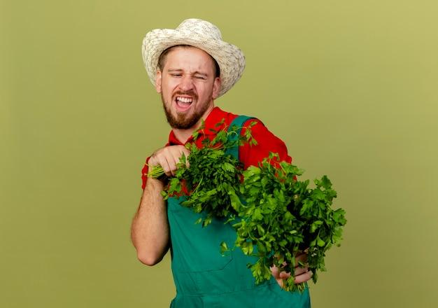 Verärgerter junger hübscher slawischer gärtner in der uniform und im hut, die koriander halten und ausstrecken, der ihn isoliert auf olivgrüner wand mit kopienraum betrachtet
