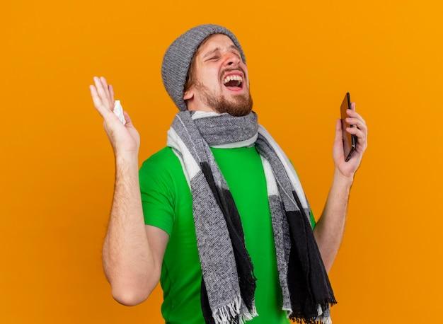 Verärgerter junger hübscher slawischer kranker mann, der wintermütze und schal hält, die handy und serviette mit geschlossenen augen lokalisiert auf orange wand hält