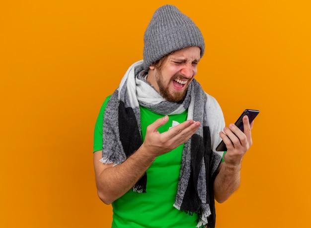 Verärgerter junger hübscher slawischer kranker mann, der wintermütze und schal hält und handy hält, das auf telefon mit serviette in der hand lokalisiert auf orange wand mit kopienraum zeigt