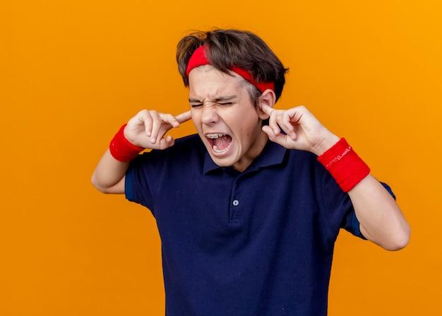 Verärgerter junger hübscher sportlicher junge, der stirnband und armbänder mit zahnspangen trägt, die finger in die ohren mit den geschlossenen augen setzen, die auf orange wand lokalisiert werden