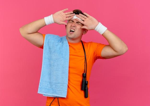 Verärgerter junger hübscher sportlicher mann, der stirnband und armbänder mit handtuch und springseil um den hals trägt und hände nahe gesicht mit geschlossenen augen lokalisiert auf rosa hält
