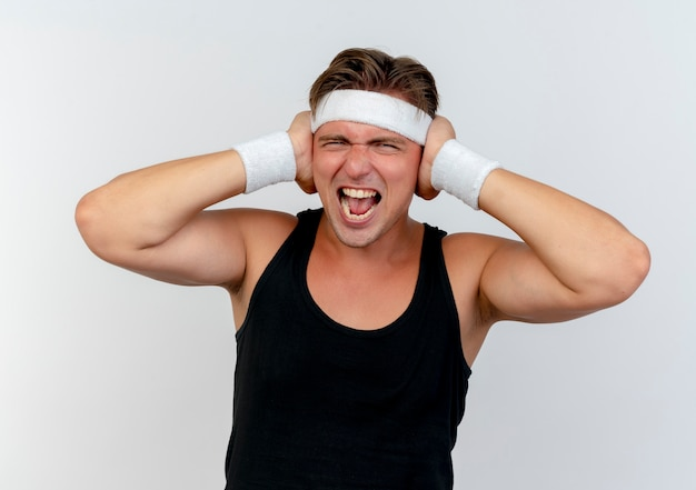 Verärgerter junger hübscher sportlicher mann, der stirnband und armbänder trägt, die hände auf ohren lokalisiert auf weiß setzen