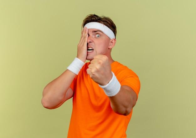 Verärgerter junger hübscher sportlicher mann, der stirnband und armbänder trägt, die hand auf gesicht setzen und faust strecken, die auf olivgrün mit kopienraum isoliert wird