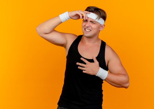Verärgerter junger hübscher sportlicher mann, der stirnband und armbänder trägt, die seite betrachten hände auf stirn und auf brust lokalisiert auf orange setzen