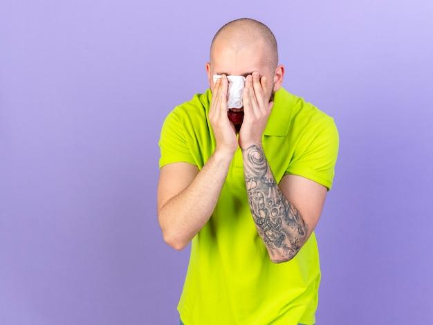 Verärgerter junger kaukasischer kranker mann bedeckt augen mit gewebe, das auf lila wand mit kopienraum isoliert wird
