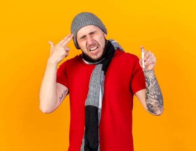 Verärgerter junger kaukasischer kranker mann, der wintermütze und schal trägt, gestikuliert waffenhandzeichen