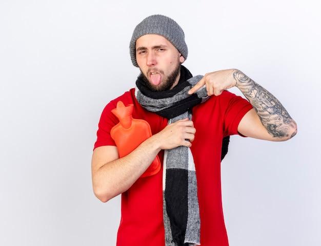 Verärgerter junger kaukasischer kranker mann, der wintermütze und schal trägt, steckt zunge heraus und hält wärmflasche lokalisiert auf weißer wand mit kopienraum