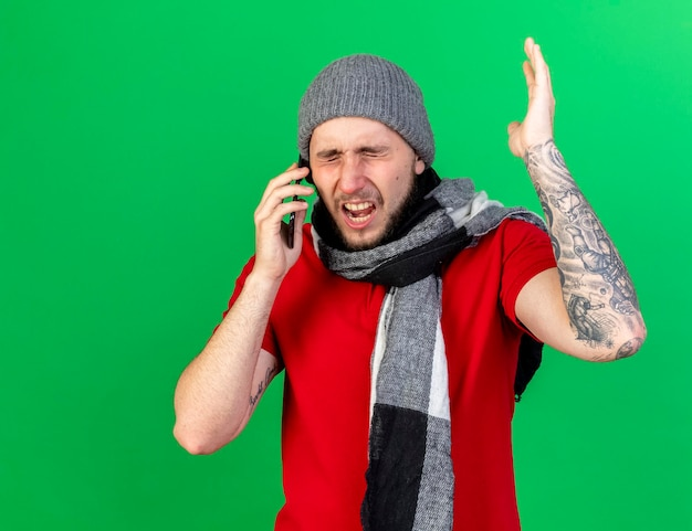 Verärgerter junger kaukasischer kranker mann, der wintermütze und schal trägt, steht mit erhabener hand, die am telefon spricht