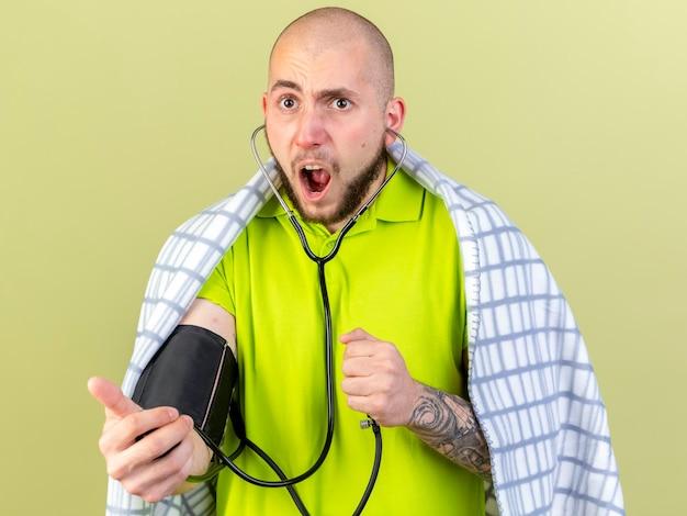 Verärgerter junger kaukasischer kranker mann mit kariertem messdruck, der blutdruckmessgerät auf olivgrün hält